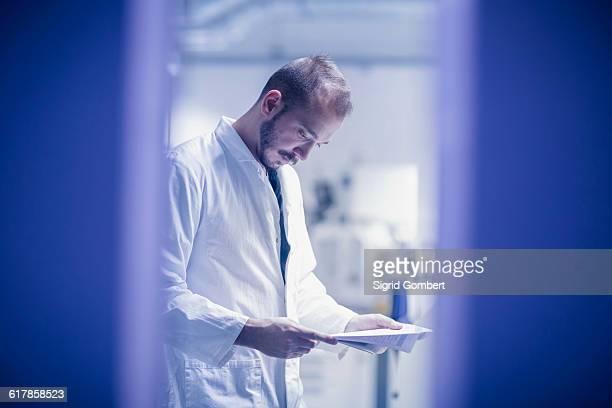 """young male scientist looking at report in an optical laboratory, freiburg im breisgau, baden-w��rttemberg, germany"" - sigrid gombert stock-fotos und bilder"