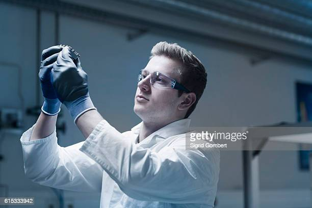 young male scientist working in an optical laboratory, freiburg im breisgau, baden-württemberg, germany - sigrid gombert stock pictures, royalty-free photos & images