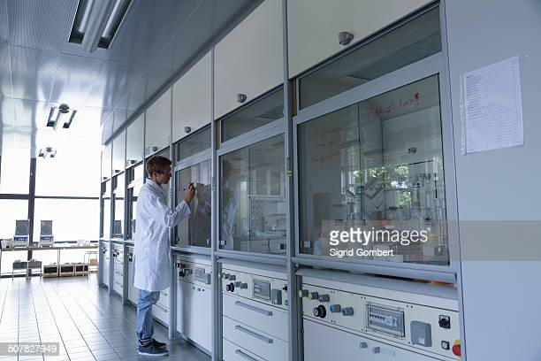 young male scientist writing on fume cupboard window - sigrid gombert stock pictures, royalty-free photos & images