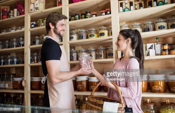 Junge männliche Verkäuferin ein Kunde in einem Null-Abfall-Geschäft tätig.