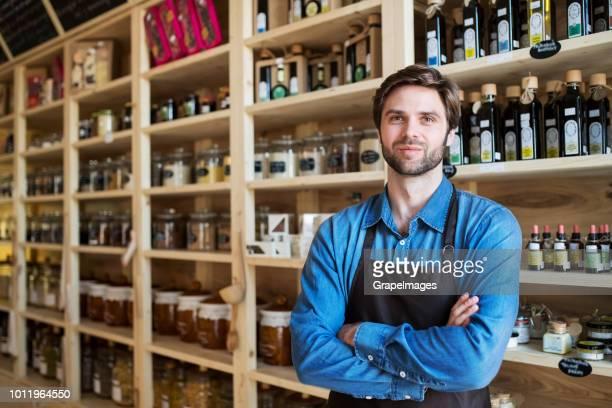Junge männliche Verkäuferin in einem Null-Abfall-Geschäft stehen, Verschränkte Arme.