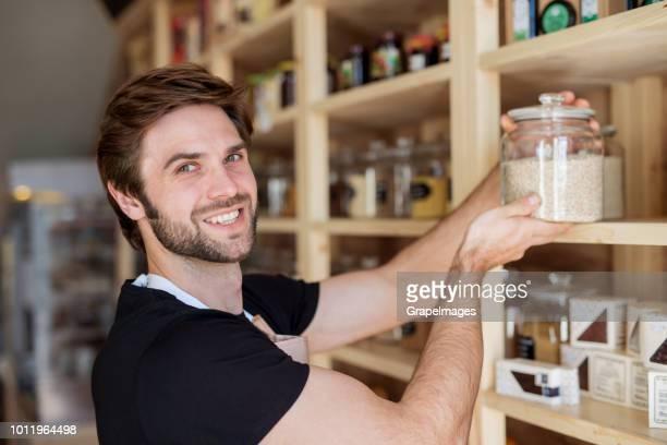 Junge männliche Verkäuferin in einem Null-Abfall-Geschäft tätig.