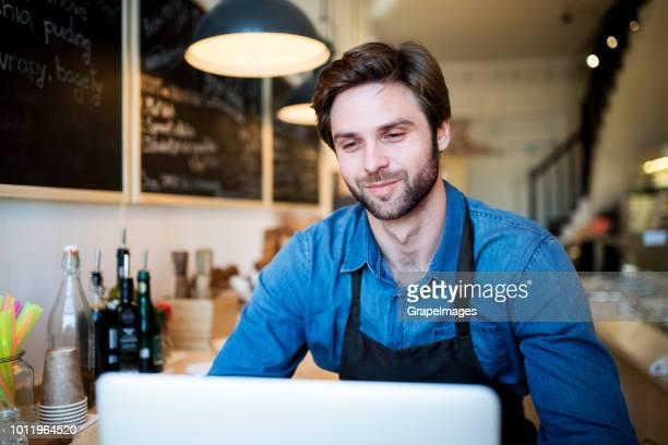 Junge männliche Verkäuferin in einem Null-Abfall-Geschäft, arbeiten mit Laptop.