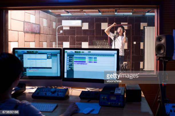 young male singer singing in studio,technician in foreground - recording studio stock pictures, royalty-free photos & images