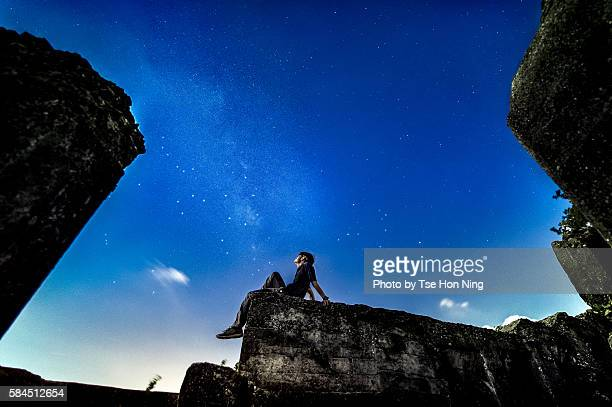 A young male sitting looking up the milky way on the sky
