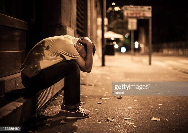 young male sitting on stairs alone on the street - binge drinking stock photos and pictures