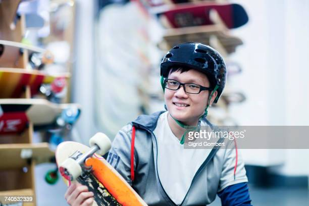 young male skateboarder holding skateboard in skateboard shop - sigrid gombert stock pictures, royalty-free photos & images