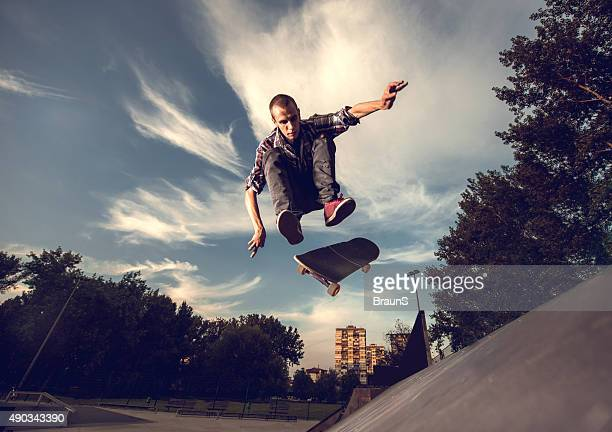 Young male skateboarder in action against the sky.