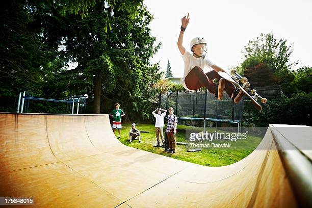 young male skateboarder in mid air on halfpipe - half pipe stock pictures, royalty-free photos & images