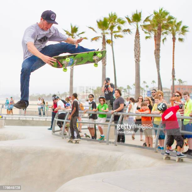 Young male skateboarder listens to music while he performs big air tricks while onlookers watch in awe at the skate park in Venice Beach, CA.
