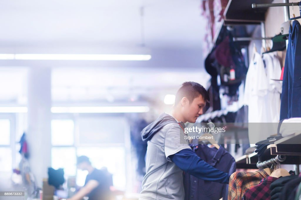Young male skateboarder looking at shirt in skateboard shop : Stock-Foto