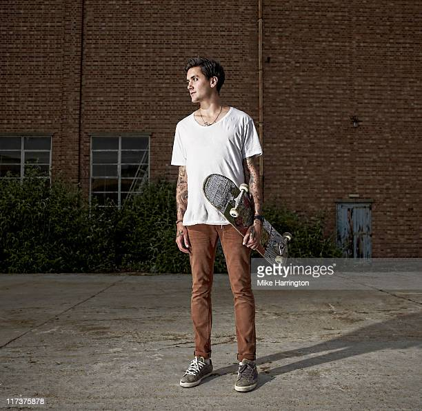 Young Male Skateboarder Standing By Urban Building