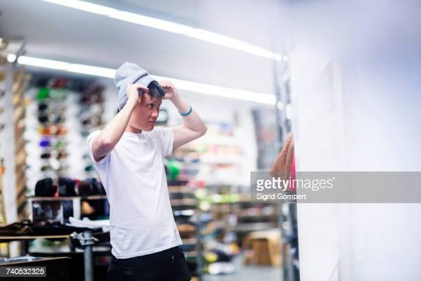 young male skateboarder trying on knit hat in skateboard shop - sigrid gombert stock-fotos und bilder