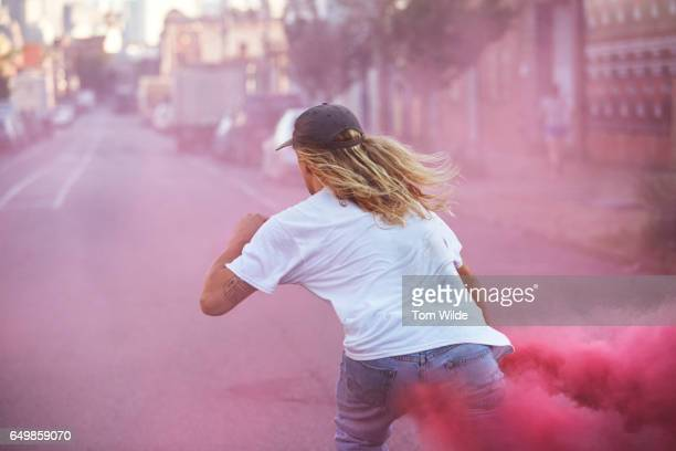 Young male skateboarder wearing white T-shirt carrying a pink flare as he skates away down the street