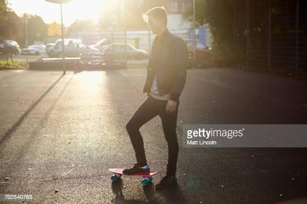 young male skateboarder with skateboard on sunlit street - só homens jovens imagens e fotografias de stock