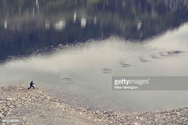 young male skimming stones - werfen stock-fotos und bilder