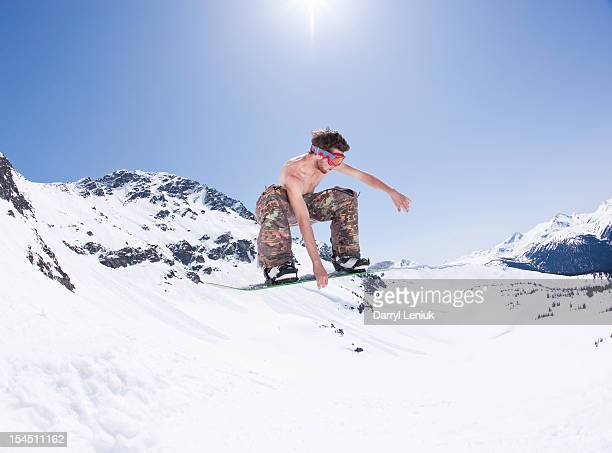 young male snowboarder jumping without a shirt - halbbekleidet stock-fotos und bilder