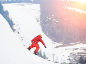 Young male snowboarder riding from the top of the snowy hill with snowboard in the evening at sunset at ski resort. Ski season and winter sports concept