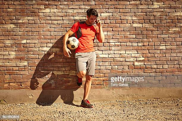 Young male soccer player chatting on smartphone on wasteland