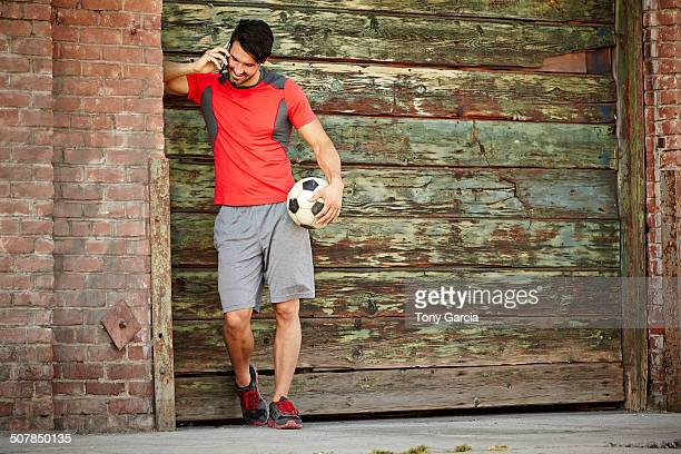 Young male soccer player chatting on smartphone