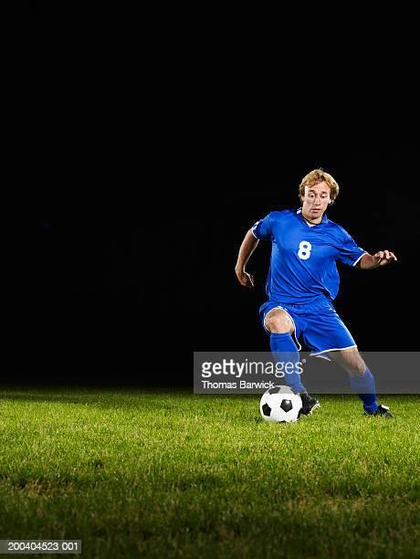 young male soccer player dribbling ball - サッカーユニフォーム ストックフォトと画像