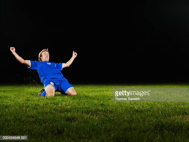 Young male soccer player sliding on field, arms raised, cheering