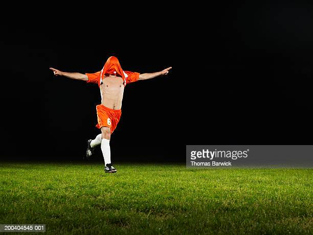 Young male soccer player with arms outstretched, jersey covering face