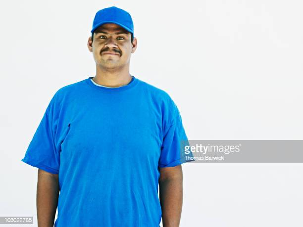 young male standing against white background  - blue hat stock pictures, royalty-free photos & images