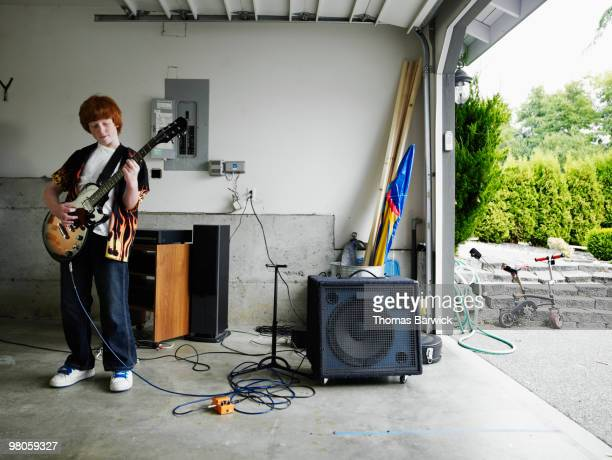 Young male standing in garage playing guitar