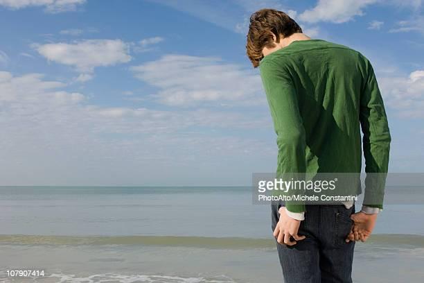 young male standing on beach with head down, rear view - blick nach unten stock-fotos und bilder