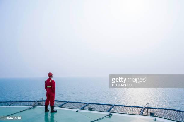 young male standing on the helicopter deck - industry stock pictures, royalty-free photos & images