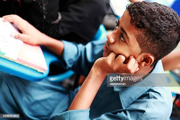 young male student attends class in street school - pakistani boys stock photos and pictures