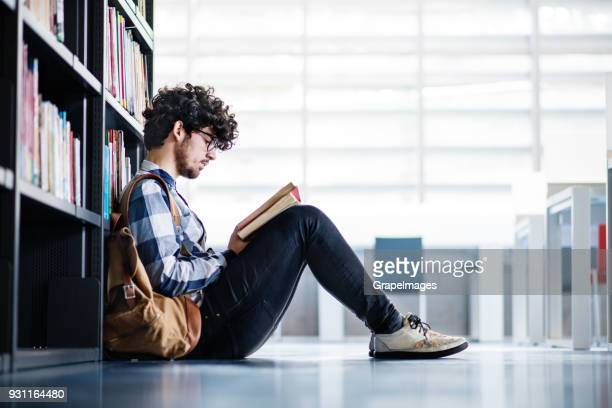 Young male student reading a book in a library.