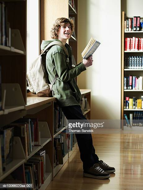 Young male student (14-15) reading in library, smiling