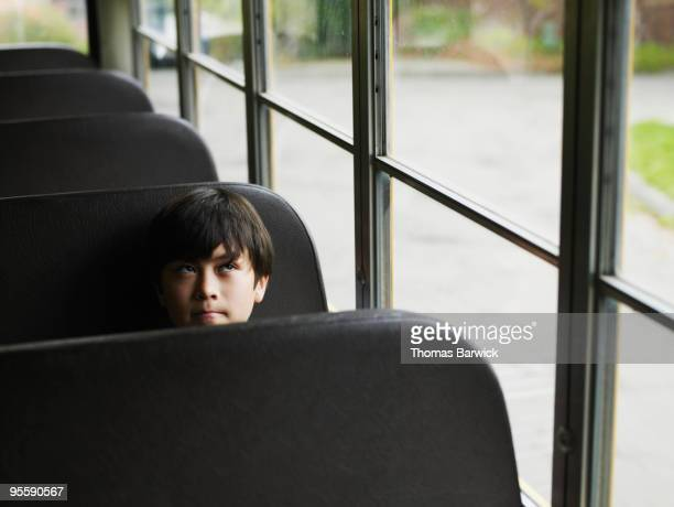 Young male student sitting on empty school bus