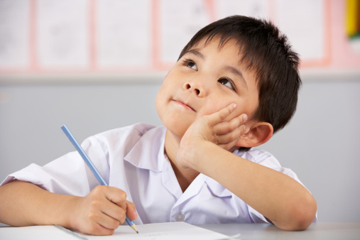 Young male student thinking at his desk in Chinese classroom 156288193
