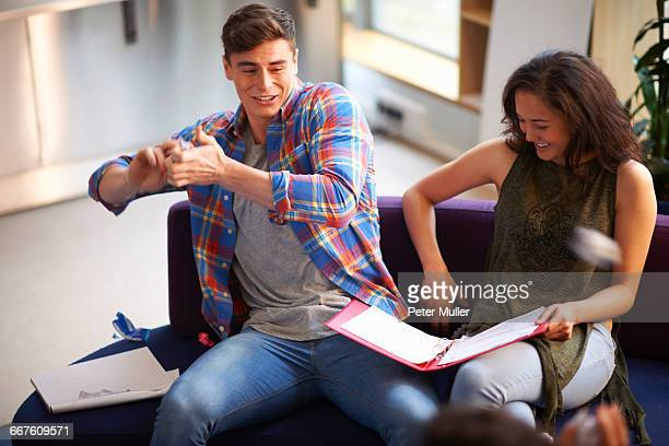 Young male student throwing crumpled paper in common room