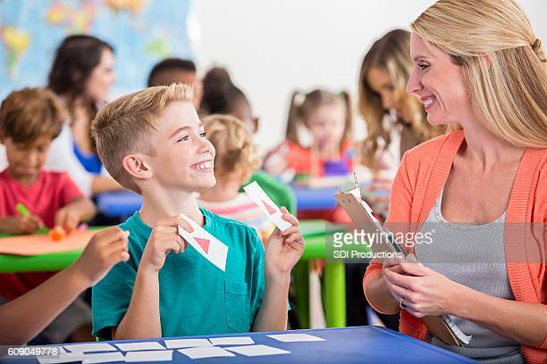 Young male student using flashcards in class with female teacher