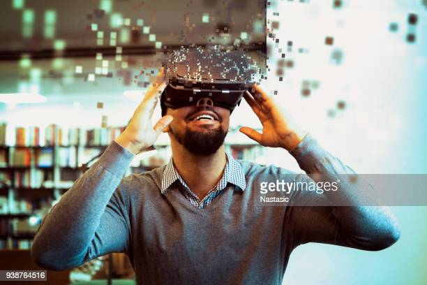 young male student using vr headset - innovation stock pictures, royalty-free photos & images