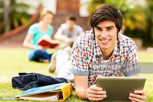 Junge männliche Studenten, die mit digitalen tablet auf dem campus