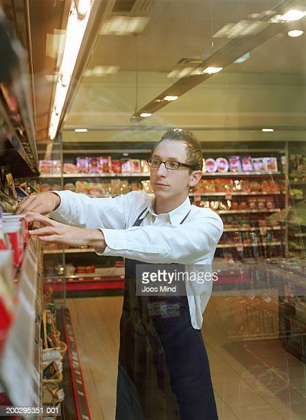 Young male supermarket assistant arranging products on shelf