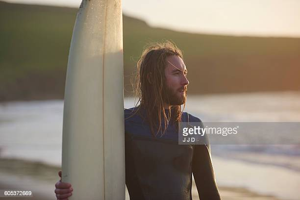young male surfer at beach, devon, england, uk - wetsuit stock pictures, royalty-free photos & images