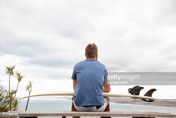 Young male surfer sitting on picnic bench looking away to sea