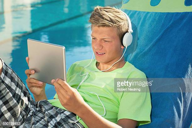 Young male swimming pool tablet computer portrait