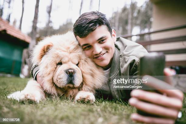 young male taking a selfie with pet chow chow dog - chow dog stock pictures, royalty-free photos & images