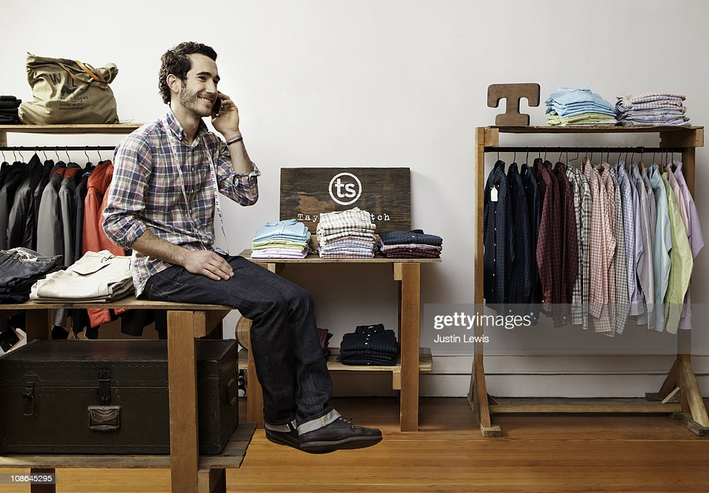 Young male talking on cell phone while shopping : Stock Photo