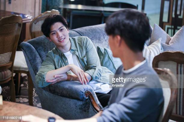 young male talking with friends while sitting at sofa at cafe - ibnjaafar stock photos and pictures
