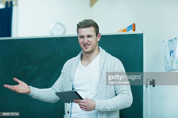 young male teacher holding a digital tablet and explaining on blackboard in classroom, freiburg im breisgau, baden-w��rttemberg, germany - sigrid gombert fotografías e imágenes de stock