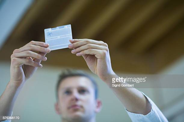 young male teacher looking at sample closely, freiburg im breisgau, baden-w��rttemberg, germany - sigrid gombert stock pictures, royalty-free photos & images