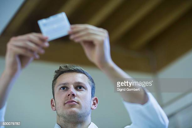 young male teacher looking at sample closely, freiburg im breisgau, baden-w��rttemberg, germany - sigrid gombert 個照片及圖片檔
